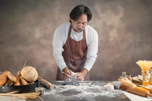 I pantaloni a vita bassa del cuoco unico impreziosiscono la pasta per pane sul bordo di legno