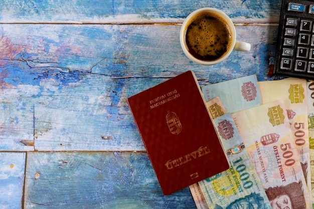 I passaporti ungheresi e diversi fiorini ungheresi banconote con tazza di caffè delizioso al tavolo calcolatrice