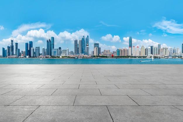 I pavimenti di marmo vuoti e lo skyline degli edifici urbani di qingdao.
