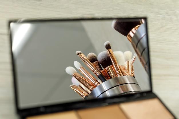 I pennelli per il trucco si riflettono in uno specchio palette con ombre