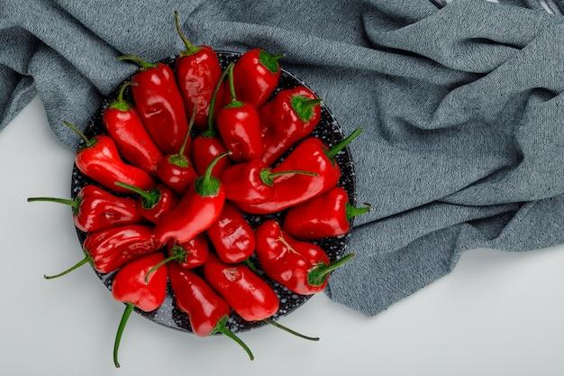 I peperoni in un piatto piatto giacciono su bianco e parete tessile