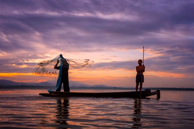 I pescatori casting stanno andando a pescare la mattina presto con barche di legno, vecchie lanterne e reti. concetto stile di vita del pescatore