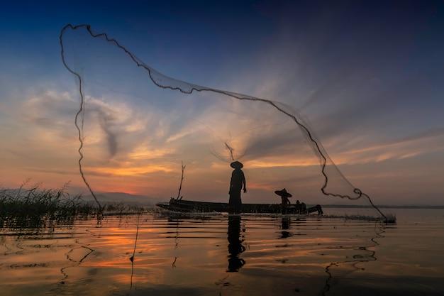 I pescatori di casting stanno andando a pescare al mattino presto con barche di legno