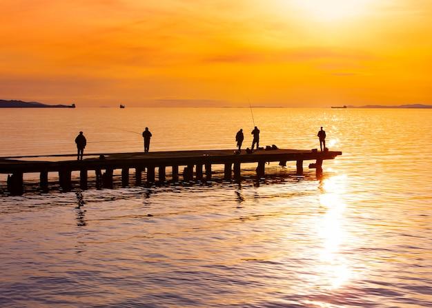 I pescatori profilano la pesca al tramonto sul vedere