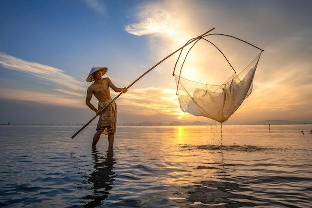 I pescatori stanno usando gli attrezzi da pesca al mattino lungo il lago songkhla