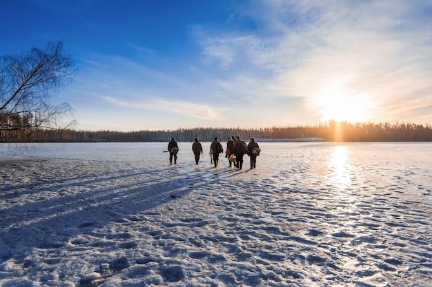 I pescatori vanno sul ghiaccio in inverno in una giornata di sole