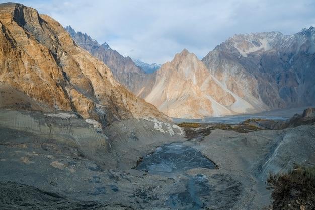 I picchi di montagna nel karakoram si estendono vicino alla morena e al lago glaciale di passu, in pakistan.