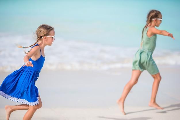 I piccoli bambini felici si divertono molto in spiaggia tropicale a giocare insieme