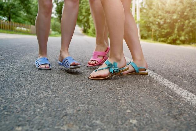 I piedi dei bambini in pantofole sull'asfalto