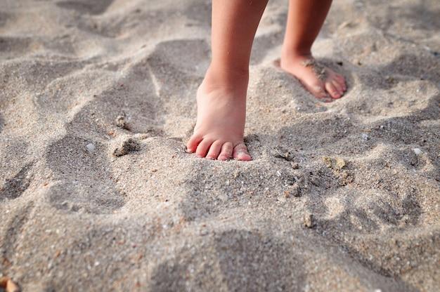 I piedi dei piccoli bambini sulla spiaggia di sabbia in estate.