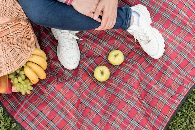 I piedi del ragazzo su una coperta da picnic