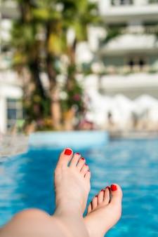I piedi della donna rilassati nella piscina