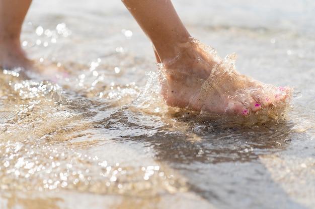 I piedi delle donne attraverso la sabbia della spiaggia e l'acqua