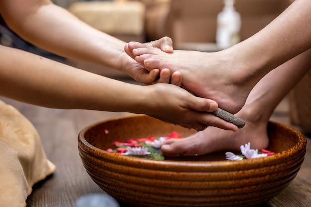 I piedi femminili per il trattamento termale sono una cura per il relax