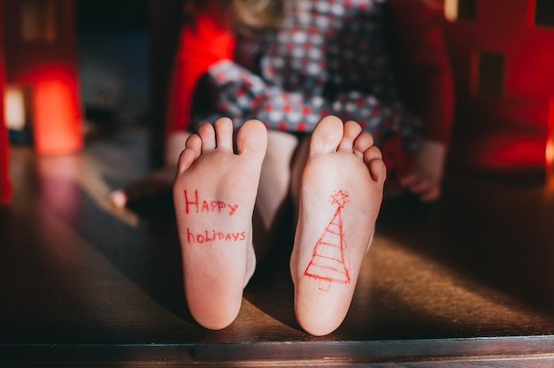 I piedi nudi del bambino sul pavimento di legno. concetto di celebrazione di natale