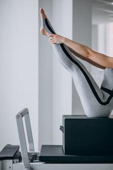I pilates di pratica della donna in un riformatore dei pilates si chiudono su