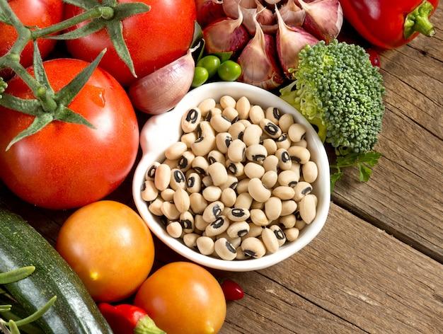 I piselli e le verdure eyed neri rasentano una fine di legno della tavola su
