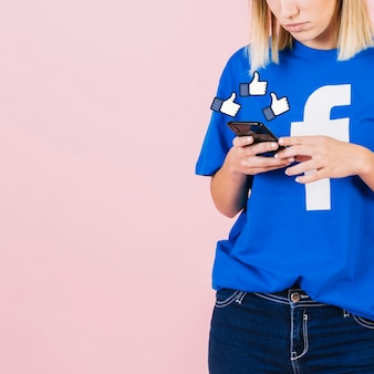 I pollici in su firmano sopra la donna che per mezzo dello smartphone