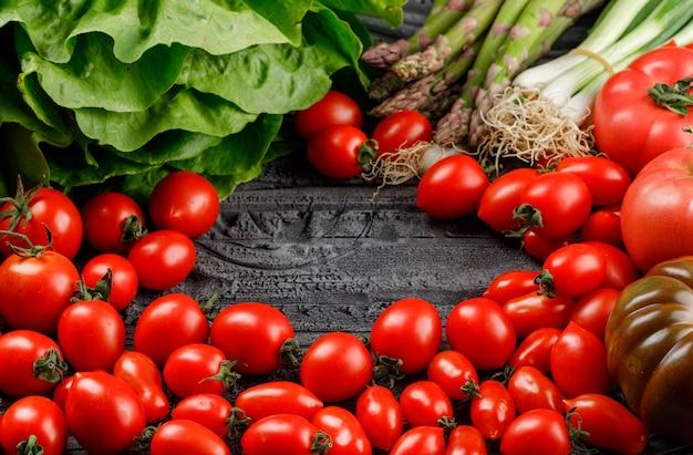I pomodori accatastano con lattuga, asparagi, cipolle verdi sulla parete di legno grigia, vista dell'angolo alto.