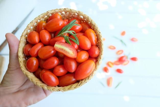 I pomodori rossi in un cestino di legno sono a disposizione.