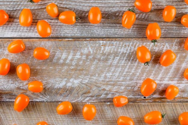 I pomodori sparsi in piano giacciono su un tavolo di legno