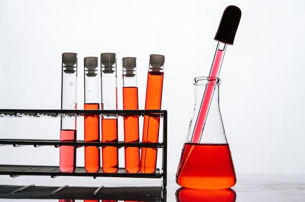 I prodotti chimici arancioni in un tubo di vetro di scienza hanno organizzato su una mensola
