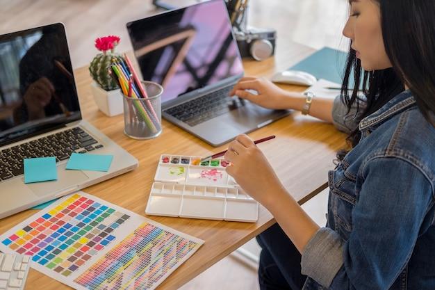 I progettisti grafici lavorano con i prodotti e i siti web di progettazione di penne e computer