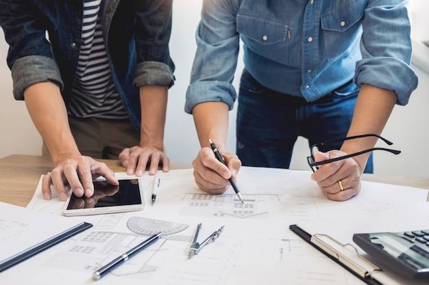 I progettisti nell'ufficio stanno lavorando a discussion blueprint architect su un nuovo progetto design draw lavoro di squadra sulla scrivania in legno.