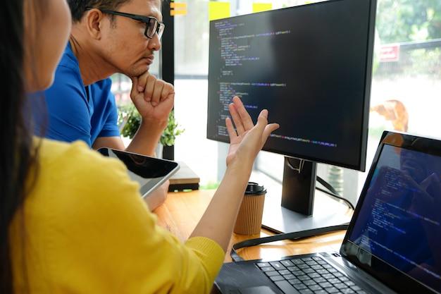 I programmatori asiatici che indossano magliette gialle stanno indicando lo schermo del loro laptop per la presentazione ai dirigenti.