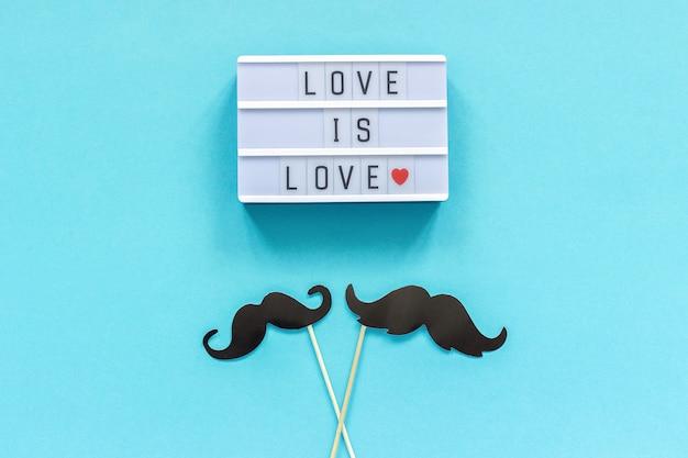 I puntelli di carta dei baffi delle coppie sul bastone e sulla scatola leggera con testo l'amore è amore su fondo blu