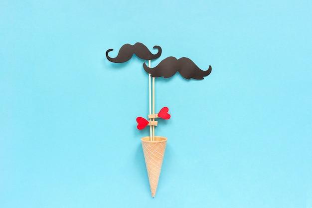 I puntelli di carta dei baffi delle coppie sul bastone hanno fissato il cuore della molletta da bucato nel cono della cialda del gelato su fondo blu