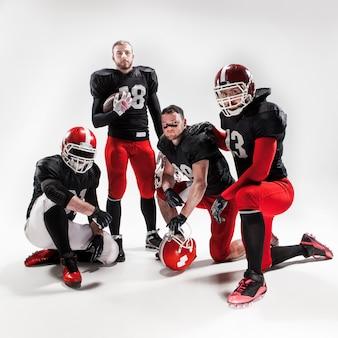 I quattro giocatori di football americano che posano con la palla su spazio bianco