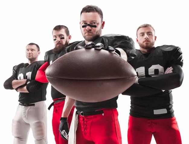 I quattro uomini di fitness caucasici come giocatori di football americano in posa a figura intera con una palla su bianco