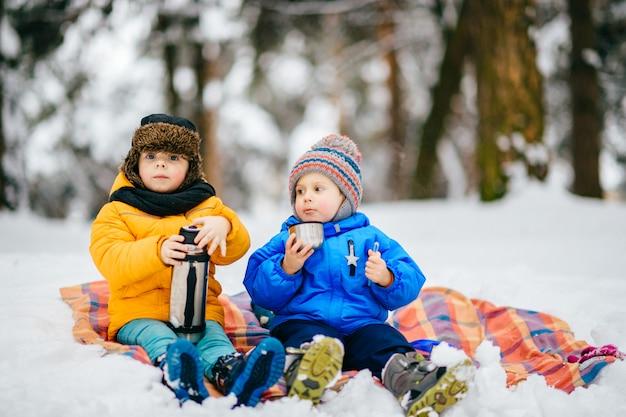 I ragazzini fanno picnic nella foresta invernale. ragazzini che bevono tè dal thermos in foresta nevosa.