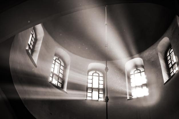 I raggi del sole si fanno strada attraverso l'alta finestra ad arco a volta