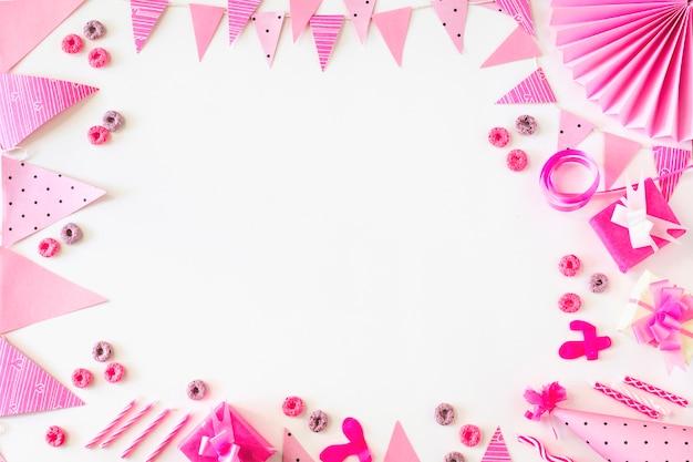 I regali di compleanno e le caramelle di cicli di froot con gli accessori del partito sul contesto bianco