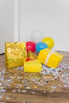 I regali; palloncini e cappello da festa con coriandoli sul pavimento in legno