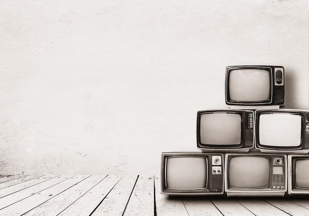 I retro televisori accatastano sul pavimento nella vecchia stanza con la parete bianca