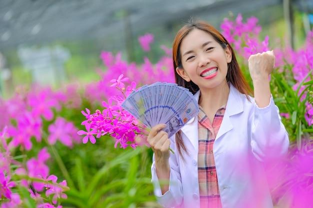 I ricercatori, donne, sono felici di riuscire nei frutteti di orchidee rosa nel giardino per l'esportazione.