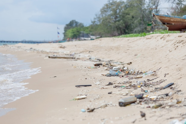 I rifiuti di plastica sulla spiaggia, svuotano le bottiglie di plastica sporche utilizzate, l'inquinamento ambientale, il concetto di problema ecologico