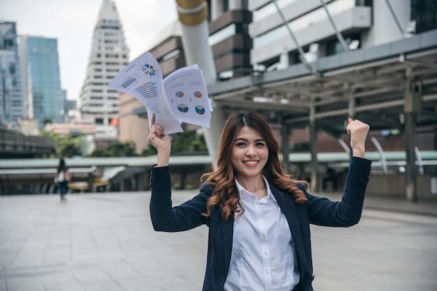 I ritratti di bella donna asiatica sembrano allegri e la fiducia è in piedi e in possesso di lavoro di carta
