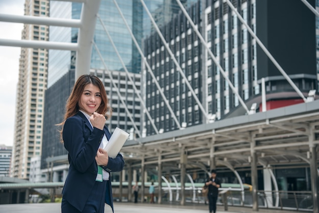 I ritratti di bella donna asiatica sembrano allegri e la fiducia è in piedi e si sente il successo