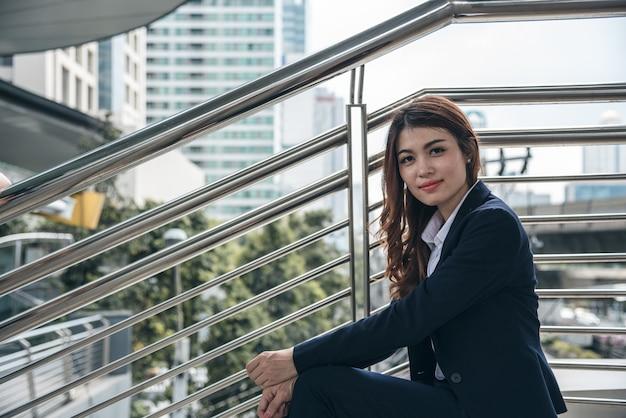 I ritratti di bella donna asiatica sembrano allegri e la fiducia è seduta all'aperto