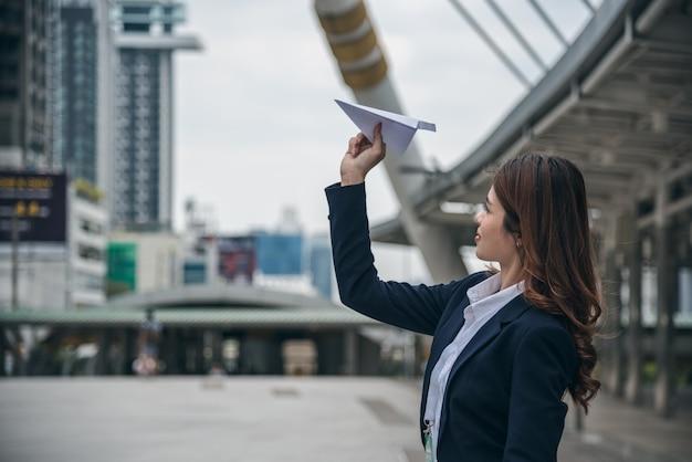 I ritratti di bella fiducia asiatica di sguardo della donna è stanti e tenenti l'aereo di carta