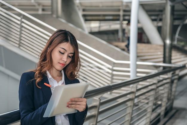 I ritratti di bella fiducia asiatica di sguardo della donna sono stanti e scriventi una nota mentre funzionano.