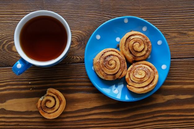 I rotoli di cannella casalinghi si trovano su un piatto blu su una tavola di legno