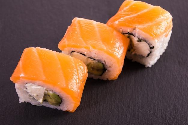 I rotoli di sushi di filadelfia california si trovano sul piatto ceramico nero