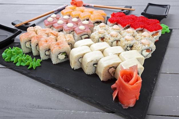 I rotoli di sushi messi sono servito sull'ardesia su fondo scuro