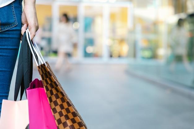 I sacchetti della spesa della tenuta della donna del primo piano camminano nel grande magazzino