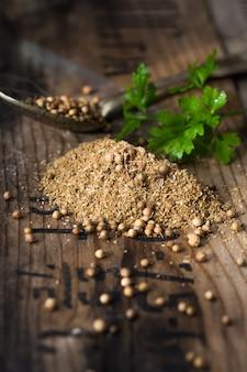 I semi di coriandolo, coriandolo verde fresco lascia su fondo di legno.